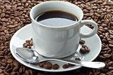 Coffee beans in white cup on saucer with spoon