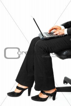 Business woman sitting on chair and using laptop.  Close-up.