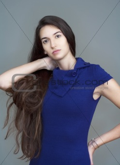 beautiful woman in blue dress with long brown hair - isolated on gray