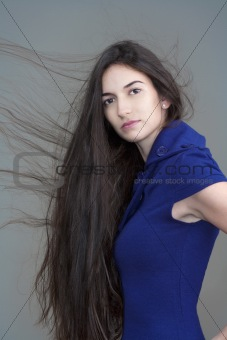 beautiful woman in blue dress with long brown hair flying - isolated on gray