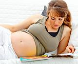Beautiful pregnant woman lying on sofa with magazine