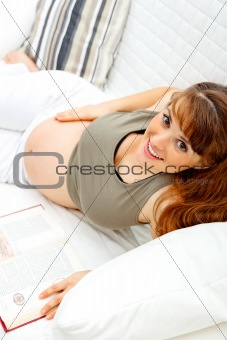 Smiling beautiful pregnant woman relaxing on sofa with book