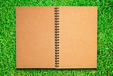 brown recycle paper notebook open on green grass field