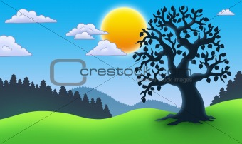 Leafy tree silhouette in landscape
