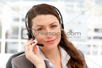 Charismatic businesswoman using earpiece sitting