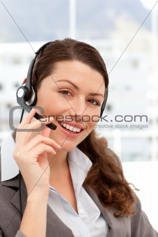 Beautiful businesswoman with headphones and smiling at the camera