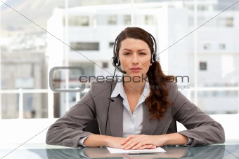 Attractive businesswoman speaking using headset sitting at a tab