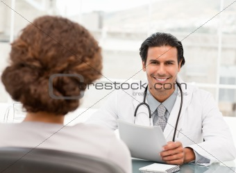 Cheerful hispanic doctor dring an appointment with a patient