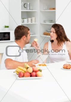 Cute woman giving bread to his husband during breakfast