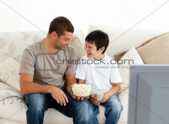 Father and son watching television while eating pop corn