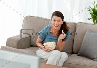 Merry woman eating pop corn while watching a movie on television
