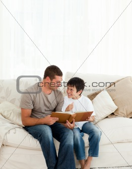 Adorable boy looking at a photo album with his father on the sof