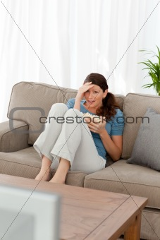 Beautiful woman watching a horror movie on television
