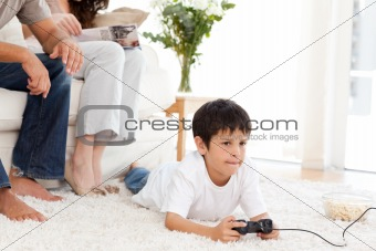 Cute boy playing video game lying on the floor at home