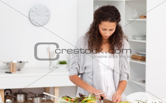 Concentrated woman cutting vegetables in the kitchen