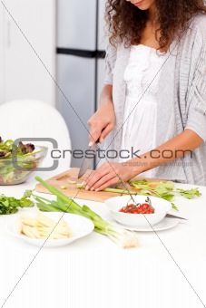Close up of a woman cutting vegetables in the kitchen