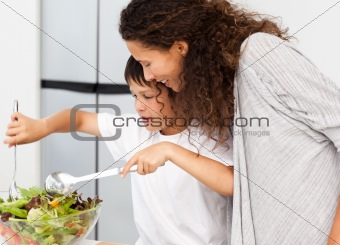 Happy mother and son preparing a salad together
