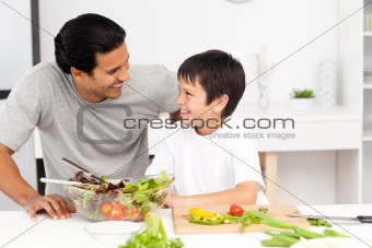 Adorable father and son looking at each other in the kitchen