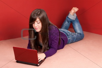Young woman with laptop lying on floor at home
