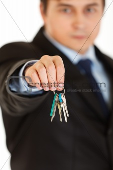 Young businessman holding keys in  hand