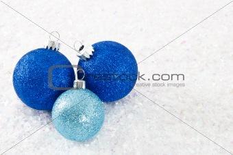 Three Blue Glittery Ornaments on Snowy Background