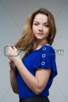 beautiful woman in blue top with long brown hair - isolated on gray