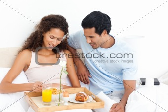 Cute woman eating cereals for breakfast lying on her bed