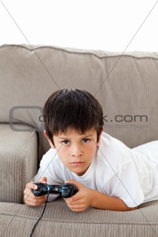 Concentrated boy playing video games lying on the sofa