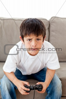 Cute boy playing video games sitting on the sofa