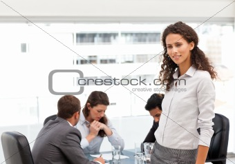 Attractive manager standing in the office while her team working