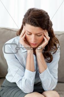 Tired businesswoman having a headache on the sofa