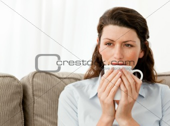 Pensive woman drinking coffee in the living room