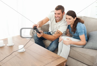 Attentive couple playing video game together in the living room