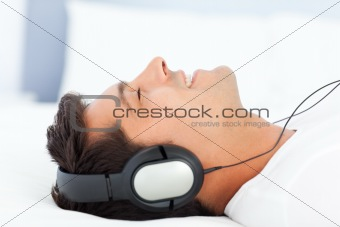 Joyful man listening music lying on his bed