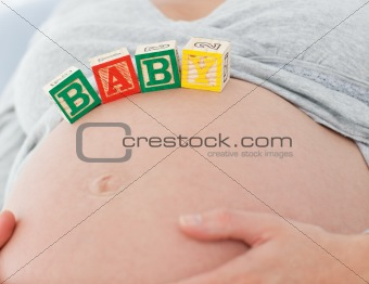 Portrait of a future mom with baby letters on her belly