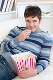 Handsome young man eating popcorn lying on the sofa