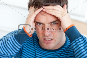 Caucasian man having a headache in the living-room
