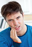 Cute caucasian man having a toothache in the living-room