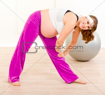 Smiling beautiful pregnant woman doing exercise  at living room