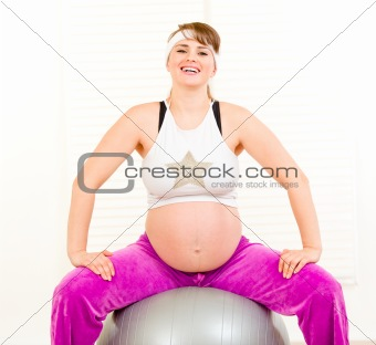 Smiling beautiful pregnant woman doing pilates exercises on gray ball at home