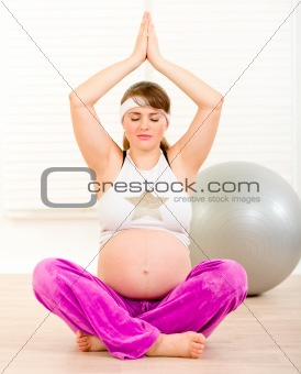 Beautiful pregnant woman doing yoga on floor at home
