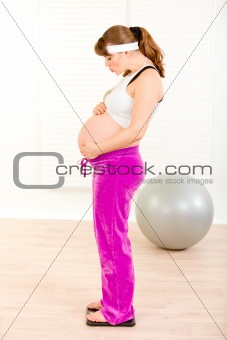 Pregnant woman standing on weight scale and blowing kiss her belly