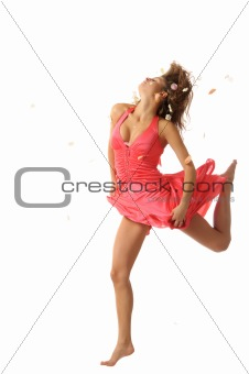 Beautiful young woman jumps with petals