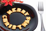 Black plate with cookies, fork and christmas decoration
