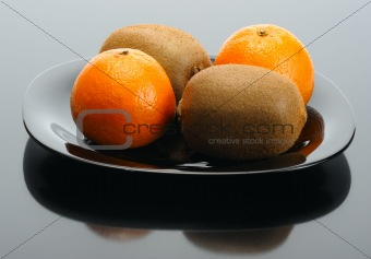 Kiwi and mandarin on a black plate