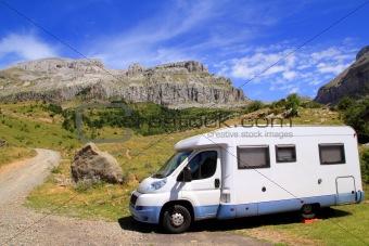 Camper van in mountains blue sky