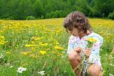 Girl picking flowers in yellow spring meadow
