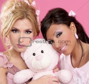 blonde and brunette girls hug a pink teddy bear