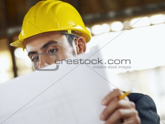 architect with blueprint in construction site
