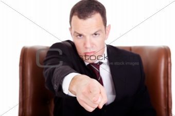 Angry businessman seated on a chair, pointing, isolated on white background. Studio shot.